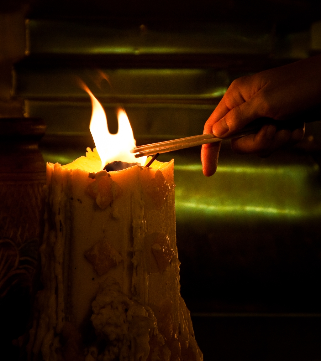 A buddhist burning incense on a candle as an offering to Buddha in Chiang Mai Thailand