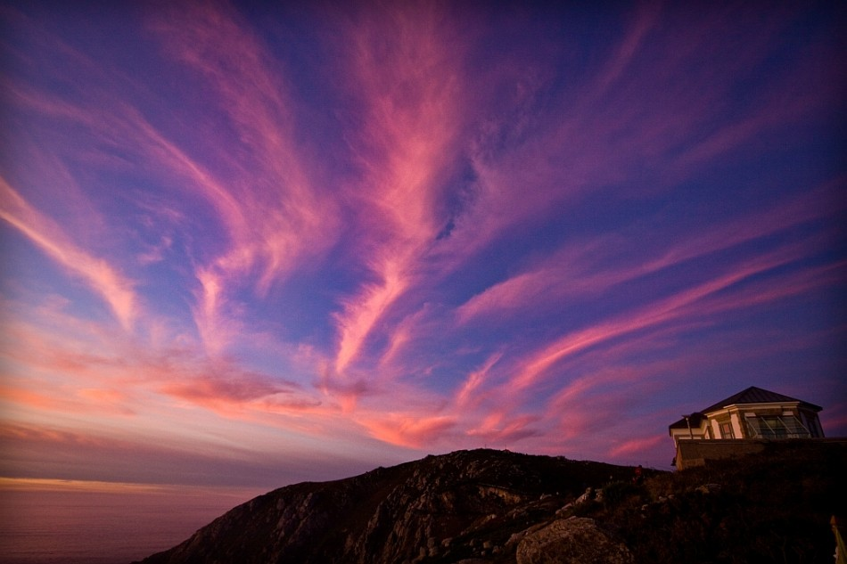 Pink weird shaped clouds creeping over the Atlantic Ocean at the end of the Camino de Santiago in Cabo Finisterra, Spain