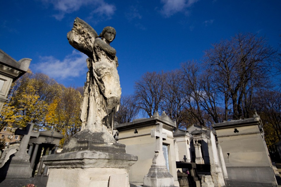 a crumbling statue of an angel over a grave in the pere lachaise cemetery in paris, france