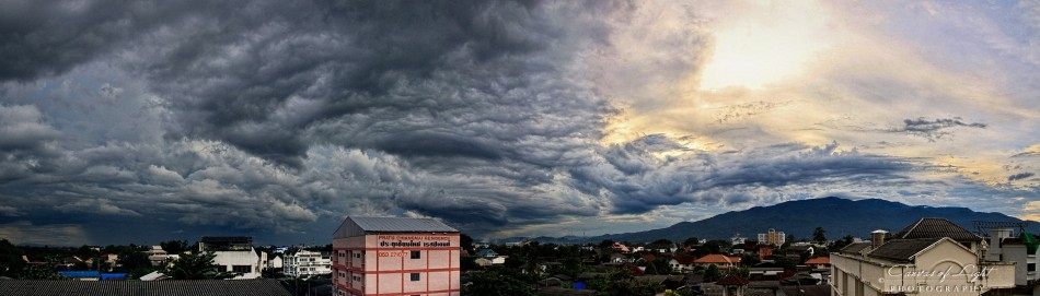 A cityscape panorama of Chiang Mai during the rainy season with a storm approaching over the mountain in Thailand.