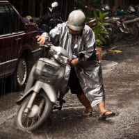 A lady stuck in the rain pushing her bike in Chiang Mai Thailand