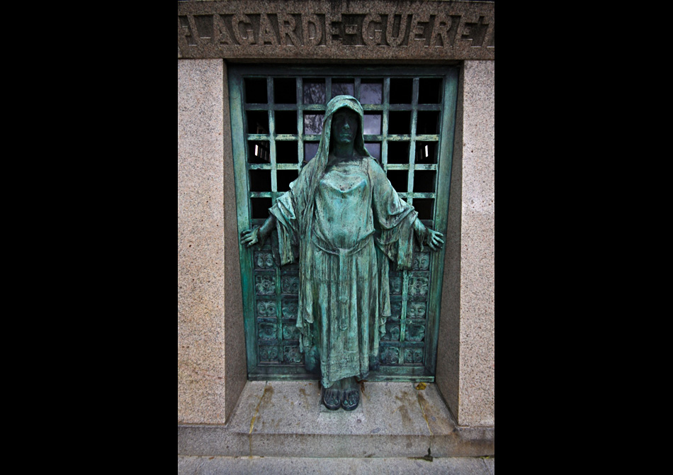 a creepy statue at the entrance of a mausoleum in Paris.